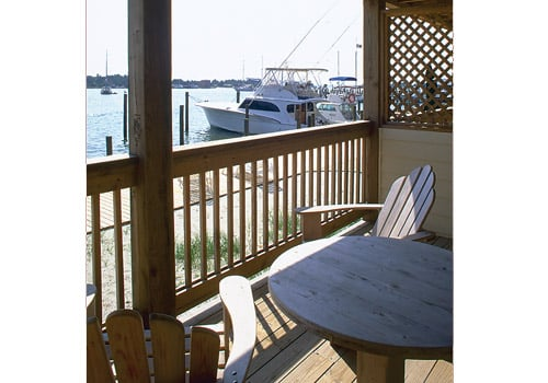4. Private deck with wooden table and Adirondack chairs overlooking docks and boat at Captain's Landing