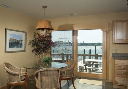 Round glass dining table and wicker chairs with sliding door showing view of Ocracoke Lighthouse