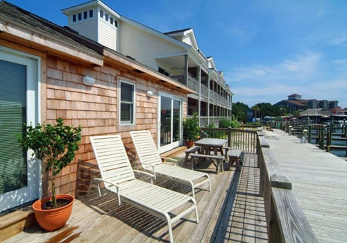 Lounge chairs, picnic table and benches on private deck of Captain's Cottage on the Harbor