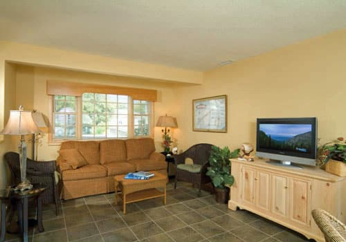 Living area of Captain's Cottage with sleeper sofa, 2 wicker chairs, flatscreen TV, tile floor