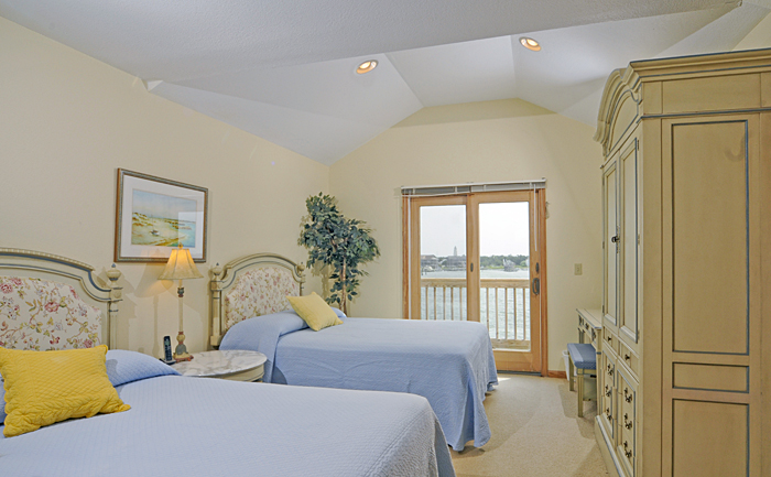 Bedroom with 2 double beds, armoire, nightstand, desk and chair, sliding door to waterfront balcony