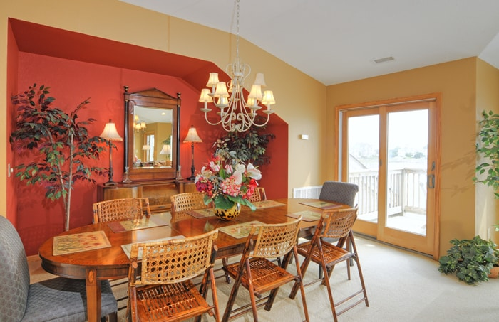 Oval dining table with chandelier and seating for 8, sliding door to waterfront balcony