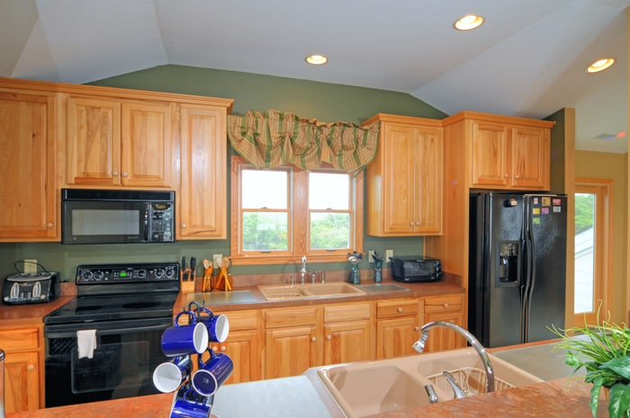 Galley kitchen with expansive countertops, double sinks, oak cabinetry, black appliances, views to Howard Street