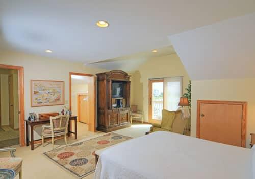 Bedroom with queen bed, desk and chair, wingback chair, walk-in closet, sliding door to balcony