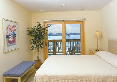 ueen bed with ivory bedspread, blue bench, nightstand with lamp, sliding door to waterfront deck